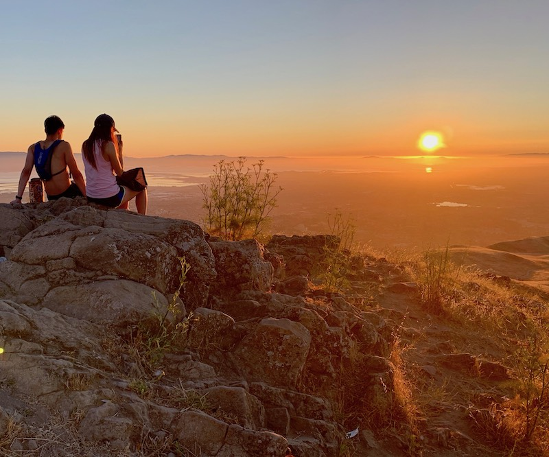 Hikers watching sunset from the summit